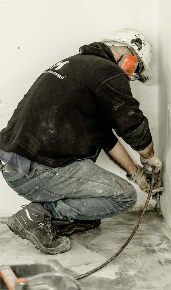 JM Totaalafdichtingen medewerker aan het werk in de bouw om wanden luchtdicht te maken